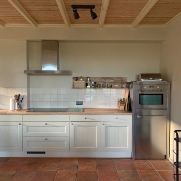 Ruime keuken met 4 pits inductie, combi magnetron oven, koelkast, vaatwasser, wasmachine