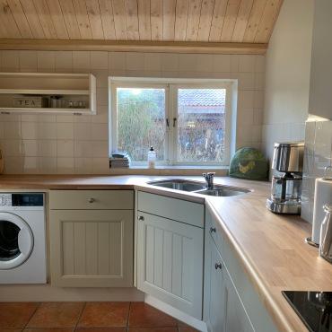 Keuken met alle apparatuur: vaatwasser, wasmachine, 4-pits inductie, afzuigkap, koelkast, combi magnetron oven, koffiezetapparaat, waterkoker