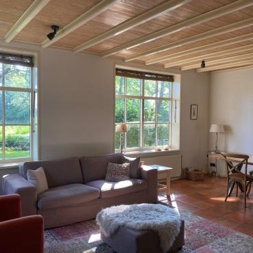 L-vormige woonkamer met houtkachel